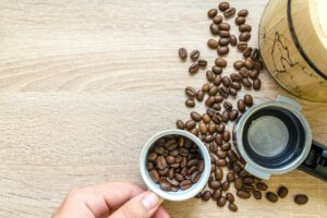 Person Holding Coffee Cup With Coffee Beans Near Coffee Press Desktop Wallpapers